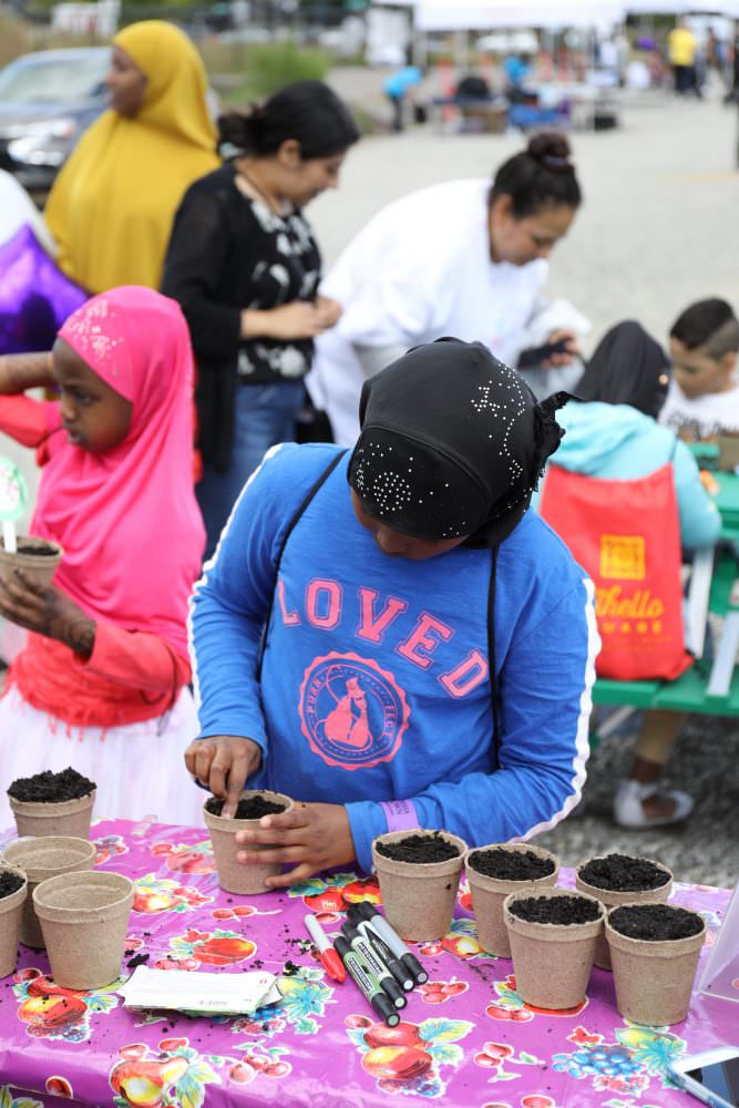 Girl planting seeds at Othello Square celebration